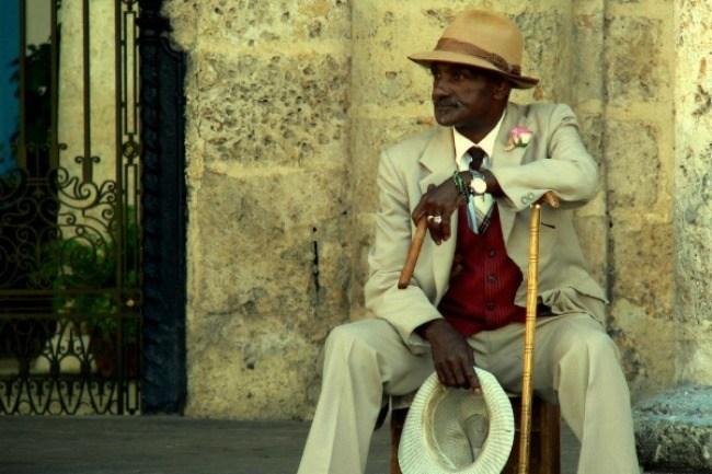 Un Cubain posé tranquillement, cigare et chapeau à la main